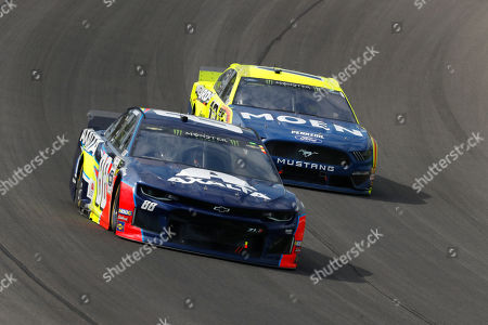 Alex Bowman (88) beats Ryan Blaney (12) into Turn 1 during a NASCAR Cup Series auto race at Michigan International Speedway in Brooklyn, Mich