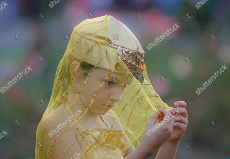 A little girl examines her traditional Turkish outfit during the Turkish festival, in Bucharest, Romania, Sunday, Aug.11, 2019. A Turkish festival of traditional music, dance and cuisine took place over the weekend in the Romanian capital