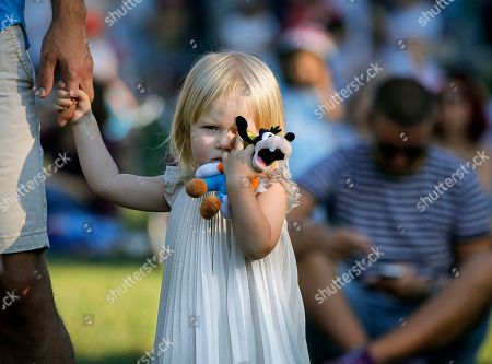 A little girl clutches a doll as she watches a performance by the Mehter Ottoman Fanfare during the Turkish festival, in Bucharest, Romania, Sunday, Aug.11, 2019. A Turkish festival of traditional music, dance and cuisine took place over the weekend in the Romanian capital