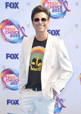 John Stamos arrives at the Teen Choice Awards, in Hermosa Beach, Calif