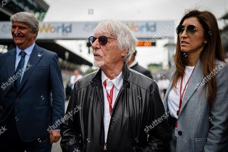 Bernie Ecclestone, Chairman Emeritus of the Formula One Group and his wife Fabiana Flosi walk through the starting grid