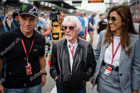 Randy Mamola, former American Grand Prix motorcycle racer, Bernie Ecclestone, Chairman Emeritus of the Formula One Group with his wife, Fabiana Flosi walk through the starting grid