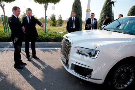 Russian Prime Minister Dmitry Medvedev, left, and Turkmenistan's President Gurbanguly Berdymukhamedov speak as they look at the Russian made limousine Aurus Senat prior to a session of the First Caspian Economic Forum in Turkmenbashi, Turkmenistan