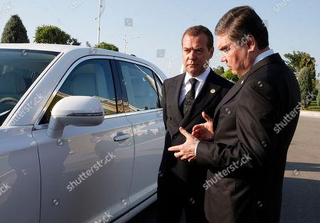 Russian Prime Minister Dmitry Medvedev (L) and Turkmenistan's President Gurbanguly Berdimuhamedow (R) speak near a Russian-built limousine Aurus Senat before a session of the First Caspian Economic Forum in Turkmenbashi, Turkmenistan, 12 August 2019.
