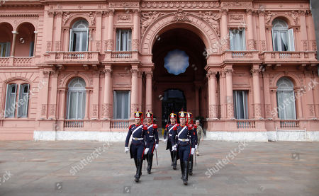 Honor guards march outside the government house where Argentine President Mauricio Macri, who is running for reelection, gave a press conference the day after primary elections in Buenos Aires, Argentina,. Macri was snubbed by voters who appeared to hand a resounding primary victory to a populist ticket with his predecessor, Cristina Fernandez de Kirchner