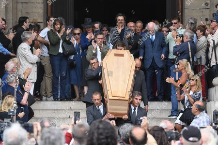 Attendees applaud Jean-Pierre Mocky as he is taken out of Saint Sulpice church