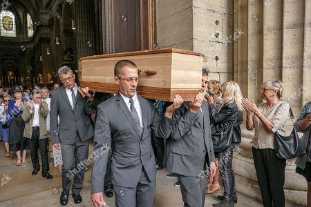 Attendees applaud as Jean-Pierre Mocky is taken out of Saint Sulpice church