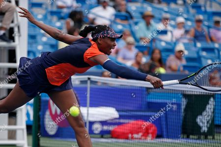 Venus Williams misses a net volley against Lauren Davis during first round play at the Western & Southern Open tennis tournament, in Mason, Ohio