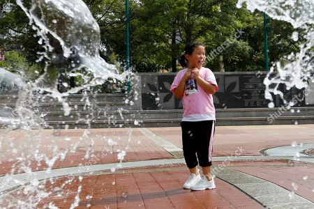 Jamie Luo, a young New York resident, cools off while playing in the Fountain of Rings in Centennial Olympic Park, in Atlanta