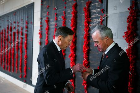 United States General (retired) David H. Petraeus (L) receives a poppy from the Director of the Australian War Memorial Brendan Nelson during a visit to the Australian War Memorial in Canberra, Australia, 13 August 2019.
