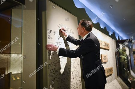 United States General (retired) David H. Petraeus signs a blast wall from Tarin Kowt during a visit to the Australian War Memorial in Canberra, Australia, 13 August 2019.