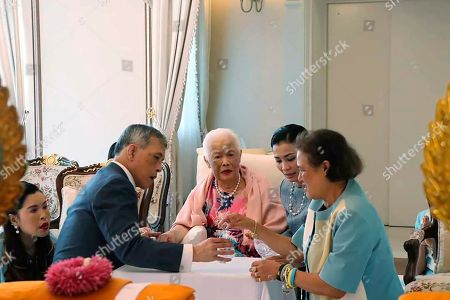 Released by The Royal Household Bureau, Thai Queen Mother Sirikit, center, is visited by her son King Maha Vajiralongkorn, Princess Chulabhorn, left, Princess Maha Chakri Sirindhorn, right, and Queen Suthida during a merit making ceremony on the queen mother's 87th birthday at the Chitralada Palace Bangkok, Thailand