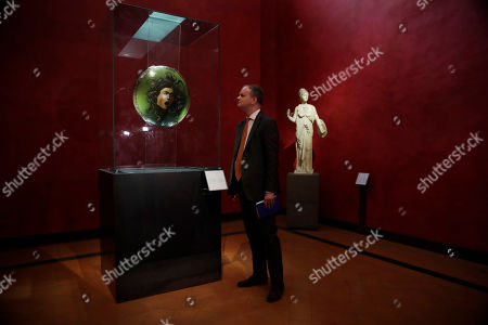 """Stock Photo of German director of the Uffizi Galleries, Eike Schmidt, admires Michelangelo Merisi da Caravaggio's 1597 painting """"Medusa"""" in a glass case, at the Uffizi Gallery museum, in Florence, Italy, . Under Schmidt's direction, entire rooms were reworked to better show off the works of Italian Renaissance masters Raphael, Michelangelo and Leonardo da Vinci, Schmidt wouldn't have been in position to do any of this without reforms enacted in 2014 by the liberal-leaning government running Italy at the time"""