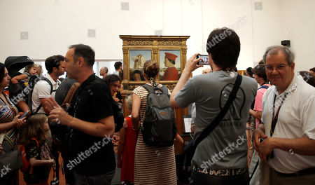 Stock Image of Visitors admire Italian Renaissance painter Piero Della Francesca's portraits of the Duke and Duchess of Urbino, Federico da Montefeltro and his wife Battista Sforza, at the Uffizi Gallery museum, in Florence, Italy, . With the paintings safely behind nearly invisible barriers, no annoying ropes need separate visitors from the paintings, and, to Uffizi Gallery director Eike Schmidt's delight, museum-goers press their noses right up against the climate-controlled display cases