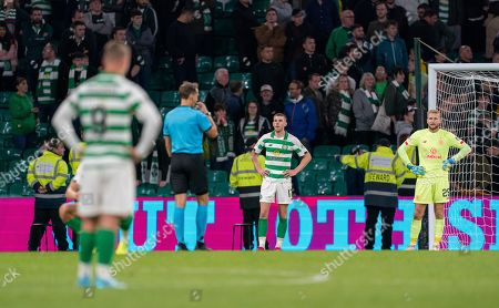 Stock Image of Celtic players Leigh Griffiths, Jozo Simunovic & Celtic goalkeeper Scott Bain stand with their hands on their hips as Referee Andrew Treimanis blows the full-time whistle after George Tucudean of CFR Cluj scored in the 97th minute to win the tie 4-3, (Agg. 5-4) to CFR Cluj.