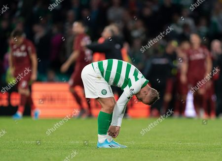 Leigh Griffiths of Celtic removes tape from his socks as CFR Cluj players celebrate in the background after George Tucudean of CFR Cluj scored in the 97th minute to win the tie 4-3, (Agg. 5-4) to CFR Cluj.