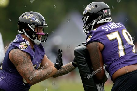 Baltimore Ravens offensive tackle Marcus Applefield, left, and offensive tackle Ronnie Stanley run a drill during NFL football training camp, in Owings Mills, Md