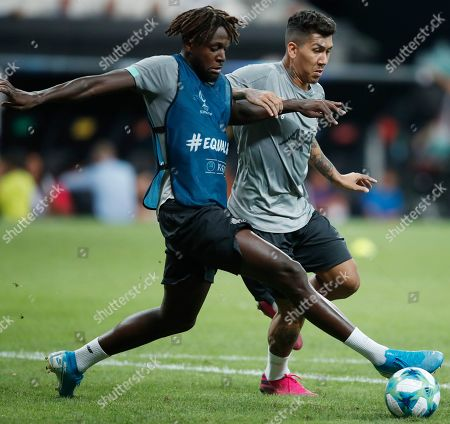 Liverpool's Dejan Lovren, right, challenges Liverpool's Divock Origi during a training session at the Besiktas Park Stadium, in Istanbul, . The winners of Champions League, Liverpool and Europa League, Chelsea will play at the Super Cup soccer match on Wednesday