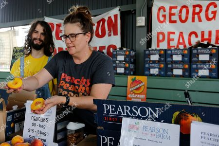 Rebecca Kern, right, and Ryder Seigle, left, sell Pearson Farm peaches and pecans at the Ponce City Farmers Market in Atlanta