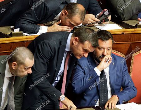 Italian Interior Minister and Deputy-Premier Matteo Salvini, right, sits beside Agricultural Minister and The League's lawmaker Gian Marco Centinaio as he addresses the Senate in Rome, . Italy's political leaders scrambled to line up allies and form alliances Tuesday as the country's right-wing interior minister pressed his demands for an early election in the hope of snagging the premiership as a platform for his anti-migrant, euroskeptic agenda. Senators hastily summoned back from a vacation break convened for a vote on scheduling their consideration of a no-confidence motion lodged by Matteo Salvini's League party against Premier Giuseppe Conte's 14-month-old populist government