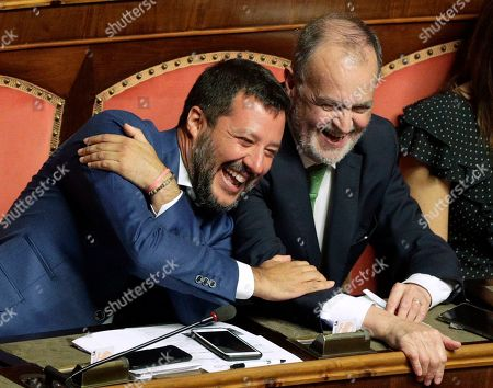 Italian Interior Minister and Deputy-Premier Matteo Salvini, left, laughs as he sits beside The League party's Roberto Calderoli, at the Senate in Rome, . Italy's political leaders scrambled to line up allies and form alliances Tuesday as the country's right-wing interior minister pressed his demands for an early election in the hope of snagging the premiership as a platform for his anti-migrant, euroskeptic agenda. Senators hastily summoned back from a vacation break convened for a vote on scheduling their consideration of a no-confidence motion lodged by Matteo Salvini's League party against Premier Giuseppe Conte's 14-month-old populist government