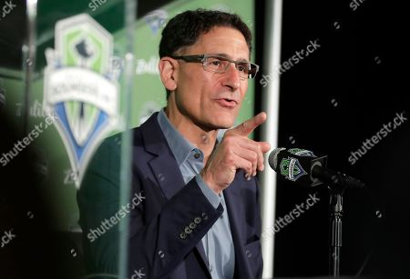Stock Image of Seattle Sounders majority owner Adrian Hanauer talks to reporters, in Seattle. Hanauer said Tuesday that the MLS soccer team is adding Seattle Seahawks NFL football quarterback Russell Wilson and his wife Ciara, hip-hop artist Macklemore, and Microsoft CEO Satya Nadella to the MLS club's ownership group, along with other investors. Hollywood producer Joe Roth, who helped bring the MLS to Seattle, is leaving the franchise