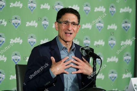 Seattle Sounders majority owner Adrian Hanauer talks to reporters, in Seattle. Hanauer said Tuesday that the MLS soccer team is adding Seattle Seahawks NFL football quarterback Russell Wilson and his wife Ciara, hip-hop artist Macklemore, and Microsoft CEO Satya Nadella to the MLS club's ownership group, along with other investors. Hollywood producer Joe Roth, who helped bring the MLS to Seattle, is leaving the franchise