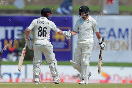 New Zealand's Henry Nichols, left, congratulates teammate Ross Taylor for scoring a half century during the day one of the first test cricket match between Sri Lanka and New Zealand in Galle, Sri Lanka