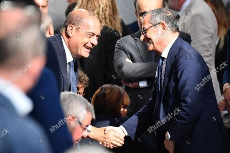 Democratic Party (PD) leader Nicola Zingaretti (L) shakes hands with Italian Economy Minister Giovanni Tria (R) prior to an official ceremony on the first anniversary of the Morandi highway bridges collapse, in Genoa, northern Italy, 14 August 2019. The motorway bridge partially collapsed on 14 August 2018, killing 43 people.