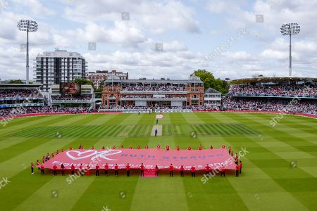 A large flag is displayed on the outfield as Andrew Strauss' children receive a guard of honour in memory of Andrew's wife Ruth during the second day of the second Specsavers Ashes series at Lord's cricket ground, London, UK