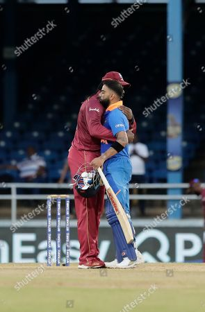 West Indies Chris Gayle, left, and India captain Virat Kohli, embrace at the end of their third One-Day International cricket match in Port of Spain, Trinidad, . India won by 6 wickets, with 15 balls remaining