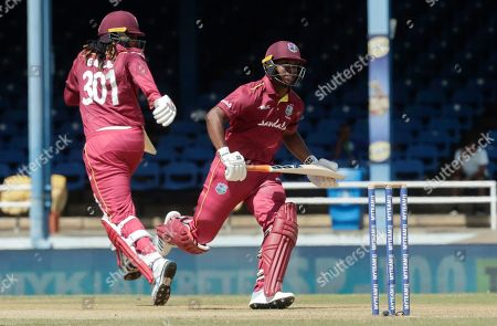 West Indies opening batsmen Chris Gayle, left, and Evin Lewis, right, run between the wickets during the third One-Day International cricket match against India in Port of Spain, Trinidad