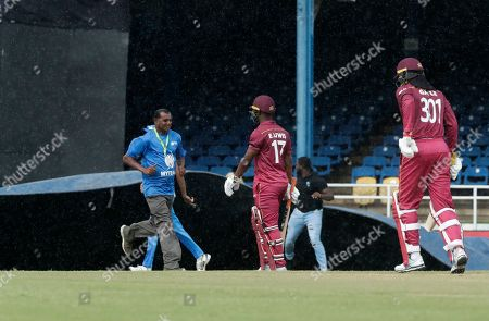 Grounds keepers pull a tarpaulin to cover the pitch as West Indies players Chris Gayle, right and Evin Lewis, center, walk back to the pavilion during a rain delay stop on the third One-Day International cricket match between India and West Indies in Port of Spain, Trinidad