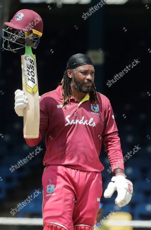 West Indies opener Chris Gayle raises his bat to the crowd after reaching a half century on the third One-Day International cricket match India in Port of Spain, Trinidad