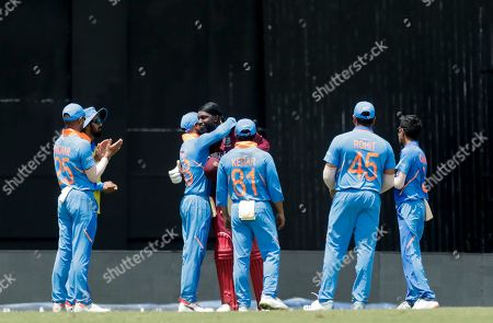 West Indies opening batsman Chris Gayle, fourth left, is congratulated by India captain Virat Kohli, third left, after Gayle was caught out by Kohli for 72 runs during their third One-Day International cricket match in Port of Spain, Trinidad