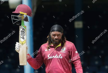 West Indies opener Chris Gayle raises his bat to the crowd after reaching a half century during the third One-Day International cricket match India in Port of Spain, Trinidad