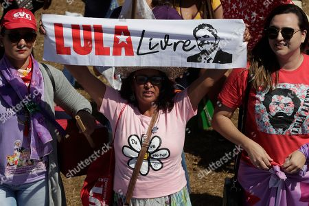 "A woman displays a banner that reads in Portuguese "" Fee Lula"" referring to imprisoned former President Luis Inacio Lula da Silva, during the Margaridas march, in front of the Brazilian National Congress, in Brasilia, Brazil, . The Margaridas, or Daisies, formed to honor Margarida Maria Alves, a murdered local leader of the Rural Worker's Union, renowned for surmounting the embedded cultural stereotypes and obstacles for women, especially those working in rural areas"
