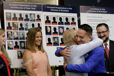 Sexual abuse victim Bridie Farrell (L) and attorney Patrick Stoneking (R) look on as fellow sexual abuse victim Joseph Caramanno, (second right,) hugs attorney Jeff Anderson (C-L) during a news conference in New York, New York,14 August 2019. On 14 August 2019 is the start of a one-year litigation window in New York allowing people to file civil lawsuits that had previously been barred by the state's statute of limitations, which was one of the nation's most restrictive before lawmakers relaxed it this year.