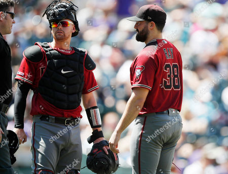 R m. From left, umpire Chris Conroy confers with Arizona Diamondbacks catcher Carson Kelly and starting pitcher Robbie Ray as he waits to be pulled from the mound before the start of the bottom of the third inning of a baseball game against the Colorado Rockies, in Denver. Relief pitcher Matt Andriese took over on the mound for Ray