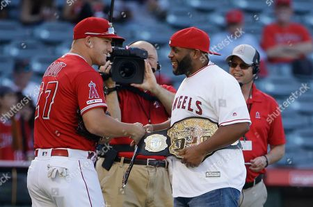 Stock Photo of Daniel Cormier, Mike Trout. UFC heavyweight champion Daniel Cormier, right, shakes hands with Los Angeles Angels' Mike Trout after Cormier threw the ceremonial first pitch before the Angels' baseball game against the Pittsburgh Pirates, in Anaheim, Calif