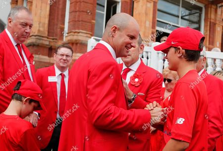 Former England cricketer Andrew Strauss, centre, is surrounded by supporters wearing red as Lord's cricket ground is turned red in aid of the Ruth Strauss Foundation, ahead of the second day of the second Ashes test match between England and Australia at Lord's cricket ground in London, . The Ruth Strauss Foundation was set up by former England cricketer Andrew Strauss in honour of his wife Ruth, who died from a rare form of lung cancer in December 2018