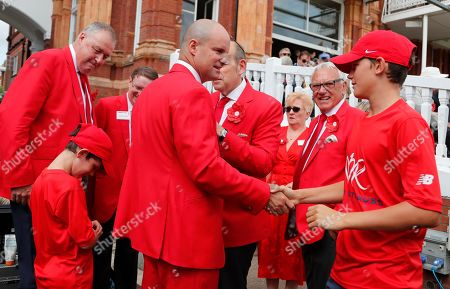 Former England cricketer Andrew Strauss, centre, is surrounded by people wearing red as Lord's cricket ground is turned red in aid of the Ruth Strauss Foundation, ahead of the second day of the second Ashes test match between England and Australia at Lord's cricket ground in London, . The Ruth Strauss Foundation was set up by former England cricketer Andrew Strauss in honour of his wife Ruth, who died from a rare form of lung cancer in December 2018
