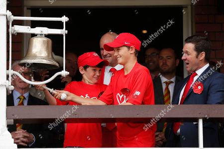 Former England cricketer Andrew Strauss, behind, with his sons Sam, right, and Luca, left, as they ring the bell, as Lord's cricket ground is turned red in aid of the Ruth Strauss Foundation, ahead of the second day of the second Ashes test match between England and Australia at Lord's cricket ground in London, . The Ruth Strauss Foundation was set up by former England cricketer Andrew Strauss in honour of his wife Ruth, who died from a rare form of lung cancer in December 2018