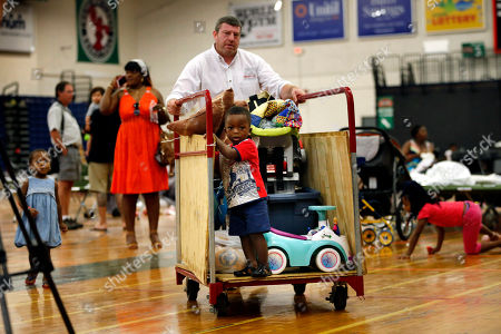 A young boy gets a ride on a luggage cart as Steve Miller helps move the belongings of African asylum seekers at the Portland Expo, in Portland, Maine. The state's largest city is racing to find homes for dozens of African asylum seekers as a temporary shelter closes on Thursday