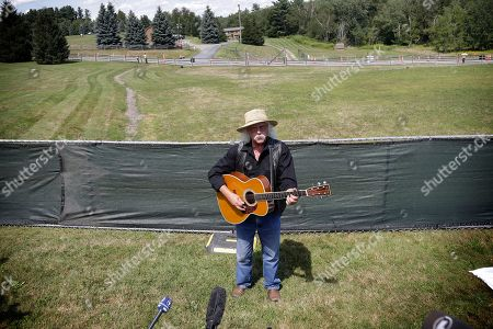 Woodstock veteran Arlo Guthrie plays a song at the original site of the 1969 Woodstock Music and Arts Fair in Bethel, N.Y., . Guthrie is schedule to play a set on the top of hill nearby but told reporters he wanted to play at least one song on the original 1969 site. Woodstock fans are expected to get back to the garden to mark the 50th anniversary of the generation-defining festival. Bethel Woods Center for the Arts is hosting a series of events Thursday through Sunday at the bucolic 1969 concert site, 80 miles (130 kilometers) northwest of New York City