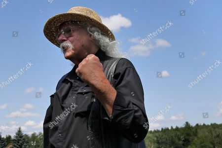 Woodstock veteran Arlo Guthrie reacts after playing a song at the original site of the 1969 Woodstock Music and Arts Fair in Bethel, N.Y., . Guthrie is schedule to play a set on the top of hill nearby but told reporters he wanted to play at least one song on the original 1969 site. Woodstock fans are expected to get back to the garden to mark the 50th anniversary of the generation-defining festival. Bethel Woods Center for the Arts is hosting a series of events Thursday through Sunday at the bucolic 1969 concert site, 80 miles (130 kilometers) northwest of New York City