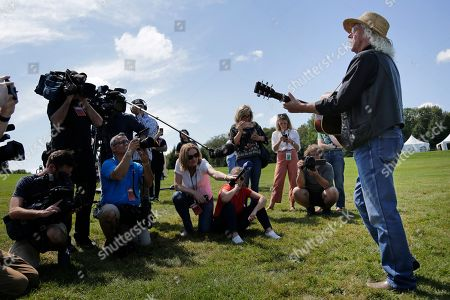 Members of the media record as Woodstock veteran Arlo Guthrie plays a song at the original site of the 1969 Woodstock Music and Arts Fair in Bethel, N.Y., . Guthrie is schedule to play a set on the top of hill nearby but told reporters he wanted to play at least one song on the original 1969 site. Woodstock fans are expected to get back to the garden to mark the 50th anniversary of the generation-defining festival. Bethel Woods Center for the Arts is hosting a series of events Thursday through Sunday at the bucolic 1969 concert site, 80 miles (130 kilometers) northwest of New York City