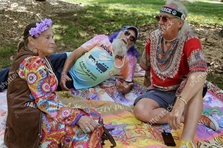"""Mary and Aaron Walkover, left, from Florida, talk with a man who calls himself """"Run-A-Way Bill"""", right, from Virginia, while waiting for the gates to open at a Woodstock 50th anniversary event in Bethel, N.Y., . Woodstock fans are expected to get back to the garden to mark the 50th anniversary of the generation-defining festival. Bethel Woods Center for the Arts is hosting a series of events Thursday through Sunday at the bucolic 1969 concert site, 80 miles (130 kilometers) northwest of New York City"""