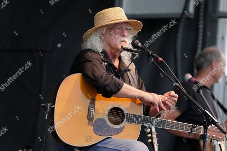 Arlo Guthrie talks during a concert at a Woodstock 50th anniversary event in Bethel, N.Y., . Bethel Woods Center for the Arts is hosting a series of events Thursday through Sunday at the bucolic 1969 concert site, 80 miles (130 kilometers) northwest of New York City