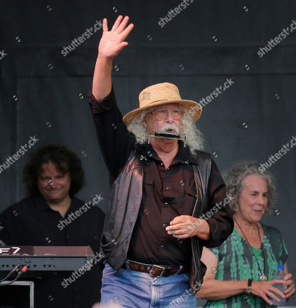 Arlo Guthrie waves to the crowd during a concert at a Woodstock 50th anniversary event in Bethel, N.Y., . Woodstock fans are expected to get back to the garden to mark the 50th anniversary of the generation-defining festival. Bethel Woods Center for the Arts is hosting a series of events Thursday through Sunday at the bucolic 1969 concert site, 80 miles (130 kilometers) northwest of New York City